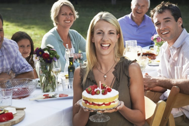 Portrait of cheerful young woman holding birthday cake with family sitting at dining table in garden