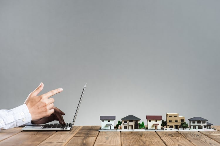 Image of a hand on laptop with small houses behind it