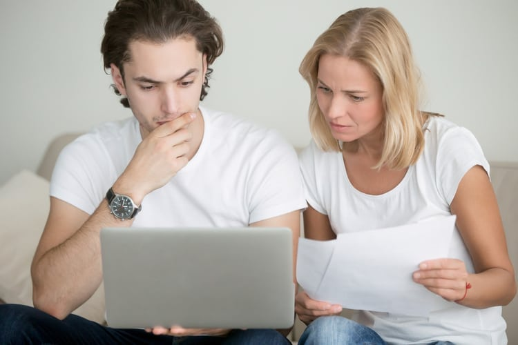Young man and woman working with laptop and holding documents