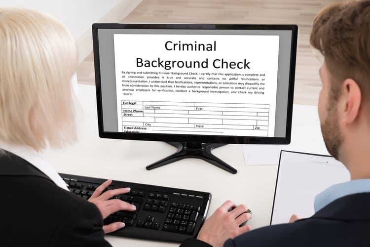 Two People Doing Criminal Background Check On Computer