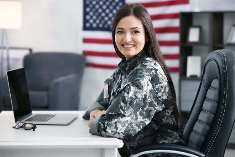 Pretty female soldier working with laptop while sitting at table