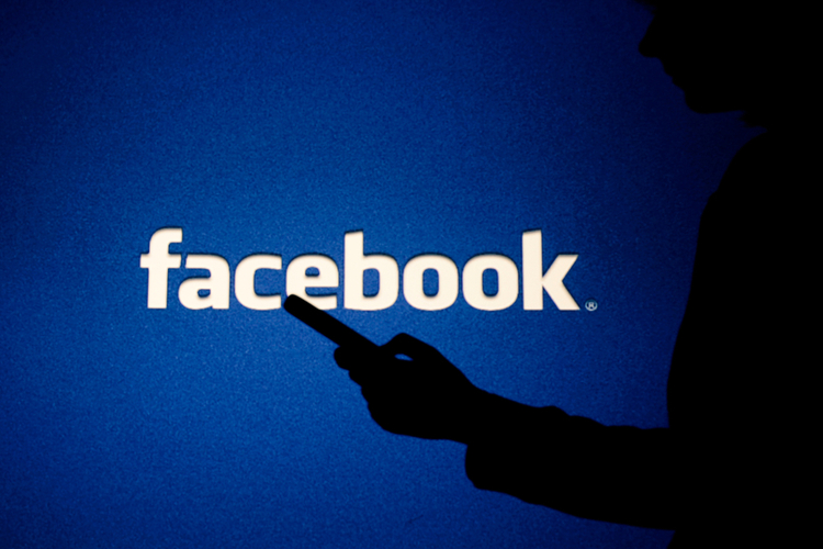 A woman looks into the smartphone in front of Facebook logo