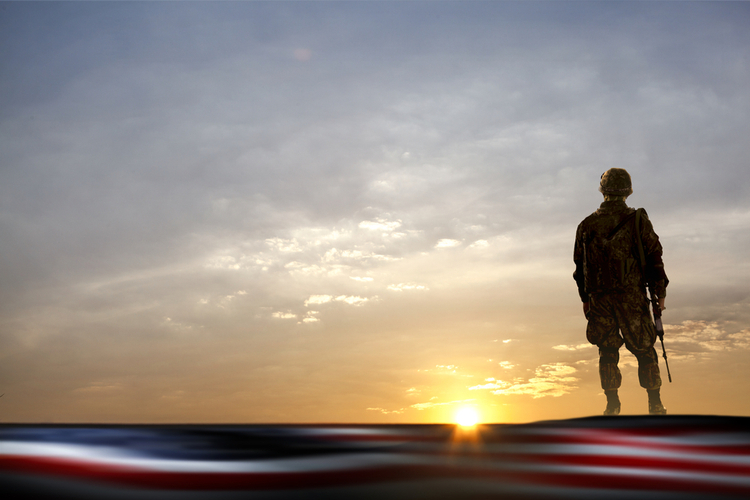 Member of military staring off into the sunset with USA flag across bottom border