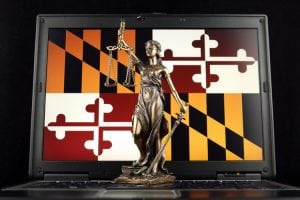 Symbol of law and justice with Maryland State Flag on laptop.