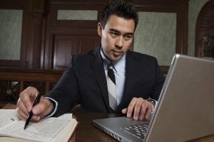 Young male advocate using laptop while preparing notes in courtroom