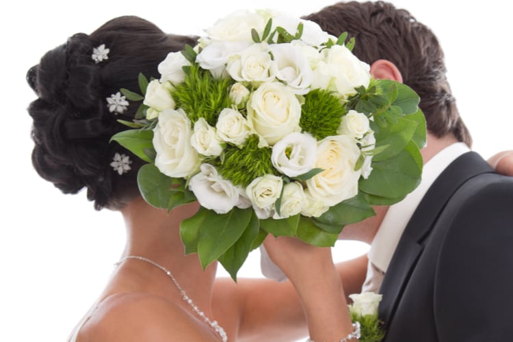 Kissing bride and groom hidden behind bride Bouquet