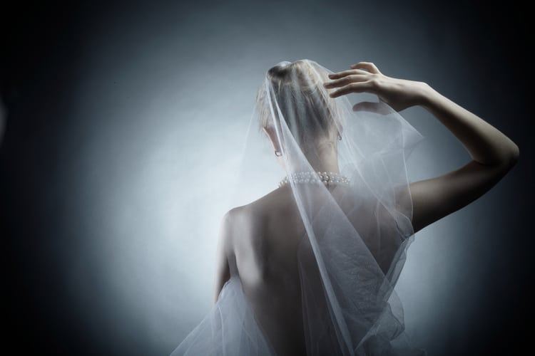 young woman in a pearl necklace tries on a wedding veil