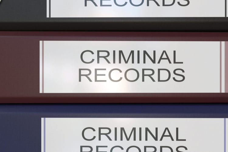 Vertical stack of multicolor office binders with Criminal records tags