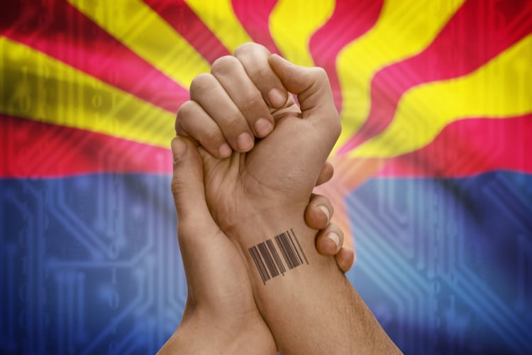 Barcode ID number tattoo on wrist of person and USA states flag on background - Arizona