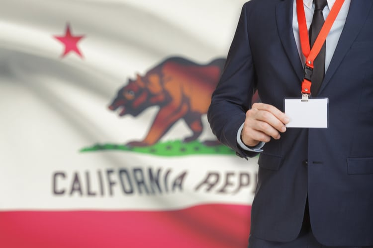 Person holding name card badge on a lanyard with US state flag on background - California