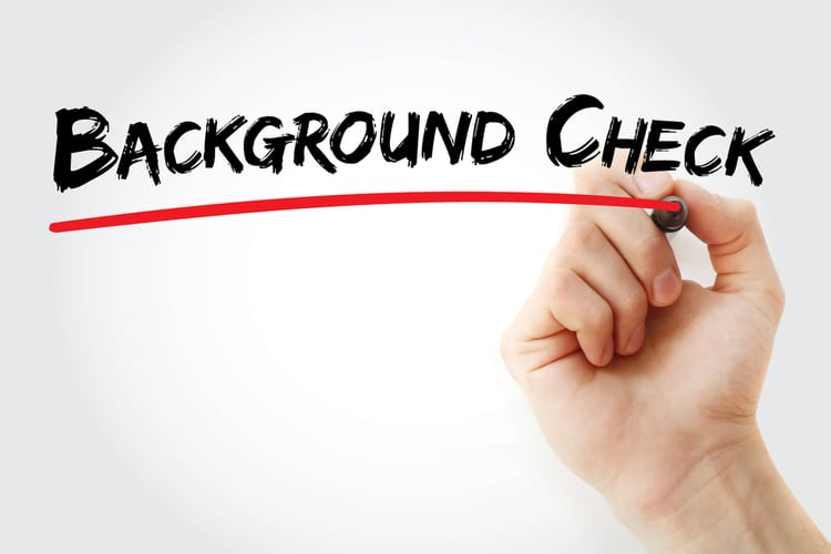 background check written in black ink with a hand making red line below
