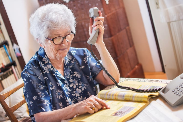 Senior woman searching yellow pages and holding telephone