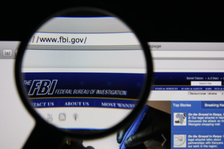 Photo of FBI homepage on a monitor screen through a magnifying glass