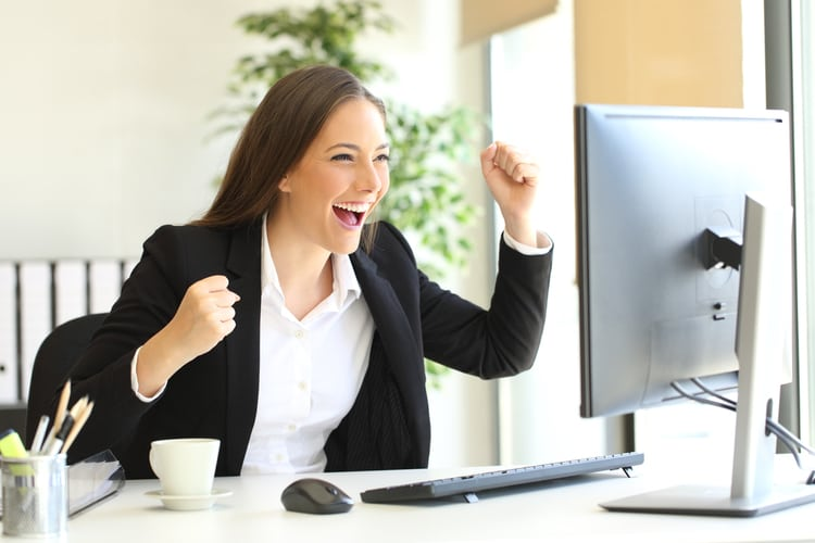 Excited executive wearing suit raising arms watching a desktop computer monitor at office