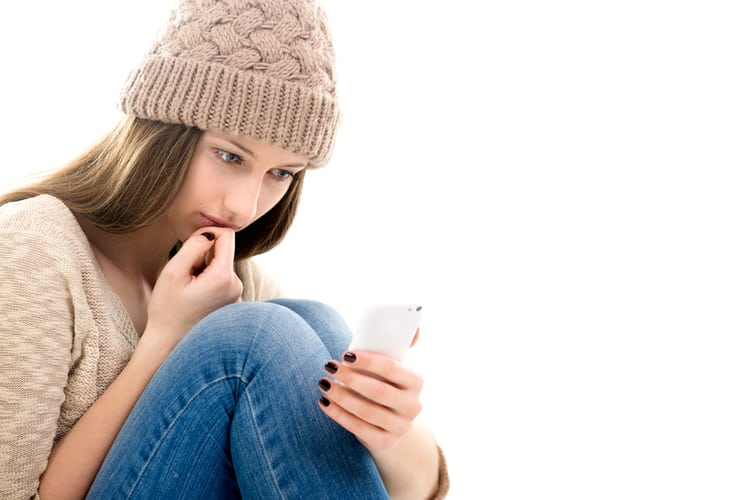 Sad teenage girl curled-up, hugging legs, feeling lonely, looking at smartphone