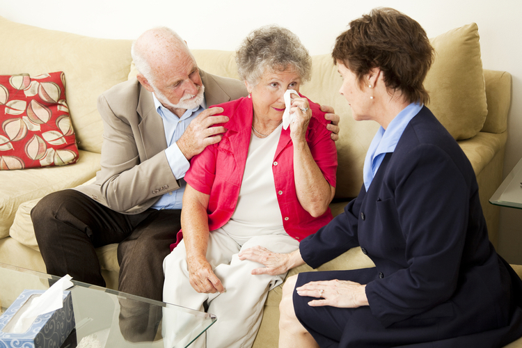 Senior couple being consoled by lady after a death