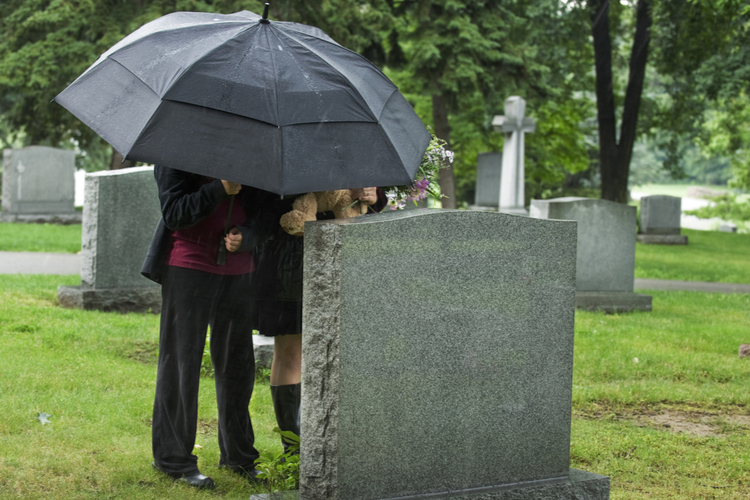 Two people under an umbrella bringing a teddy bear and flowers to a grave site in the rain.