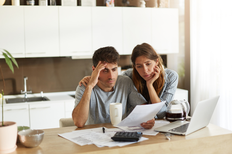 Unhappy American couple managing home accounts in kitchen